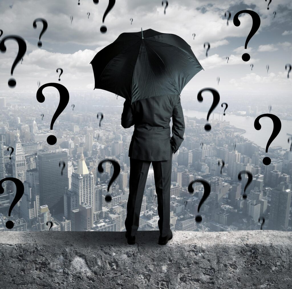 Why are you in business? What is your inner rationale? The image shows a businessman at a precipice, with question marks all around